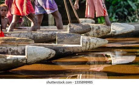 INDONESIA, IRIAN JAYA, ASMAT PROVINCE, AMANAMKAY VILLAGE - 13 JUNE 2016: Fragments of canoe warriors of the Asmat tribe on the river. On June 13, 2016 Amanamkay Village, Asmat province, Indonesia