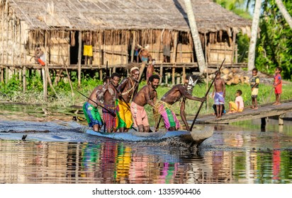 INDONESIA, IRIAN JAYA, ASMAT PROVINCE, AMANAMKAY VILLAGE - 13 JUNE 2016: Warriors of the Asmat tribe canoeing against the backdrop of a traditional village. On June 13, 2016 Amanamkay Village, Asmat p