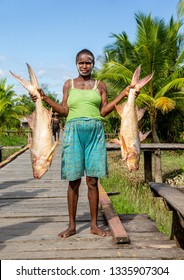 INDONESIA, IRIAN JAYA, ASMAT PROVINCE, AMANAMKAY VILLAGE - 13 JUNE 2016: Woman of the Asmat tribe is holding two big fish.. On June 13, 2016 Amanamkay Village, Asmat province, Indonesia