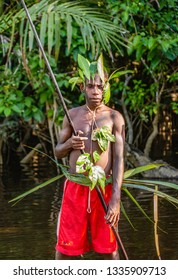 INDONESIA, IRIAN JAYA, ASMAT PROVINCE, AMANAMKAY VILLAGE - 13 JUNE 2016: Young warrior of the tribe Asmat with a spear. On June 13, 2016 Amanamkay Village, Asmat province, Indonesia