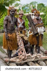 INDONESIA, IRIAN JAYA, ASMAT PROVINCE, JOW VILLAGE - JANUARY 19: Warriors Asmat tribe sits and carves a ritual statue. On January 19, 2012  Jow Village, Asmat province, Indonesia