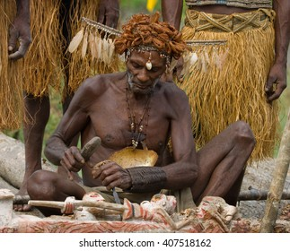 INDONESIA, IRIAN JAYA, ASMAT PROVINCE, JOW VILLAGE - JANUARY 19: Warrior Asmat tribe sits and carves a ritual statue. On January 19, 2012  Jow Village, Asmat province, Indonesia