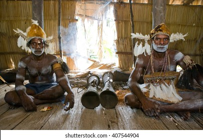 INDONESIA, IRIAN JAYA, ASMAT PROVINCE, JOW VILLAGE - JANUARY 19: Men Asmat tribe are sitting at home and play on the drum. On January 19, 2012  Jow Village, Asmat province, Indonesia