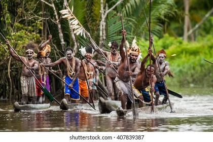 INDONESIA, IRIAN JAYA, ASMAT PROVINCE, JOW VILLAGE - JUNE 12: Warriors Asmat tribe are use traditional canoe. On June 12, 2012  Jow Village, Asmat province, Indonesia