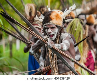 INDONESIA, IRIAN JAYA, ASMAT PROVINCE, JOW VILLAGE - JUNE 12: Asmat tribe warrior with bow and arrow. On June 12, 2012  Jow Village, Asmat province, Indonesia