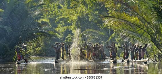 INDONESIA, IRIAN JAYA, ASMAT PROVINCE, JOW VILLAGE - MAY 23: Canoe war ceremony of Asmat people. Headhunters of a tribe of Asmat . New Guinea Island, Indonesia. May 23, 2016