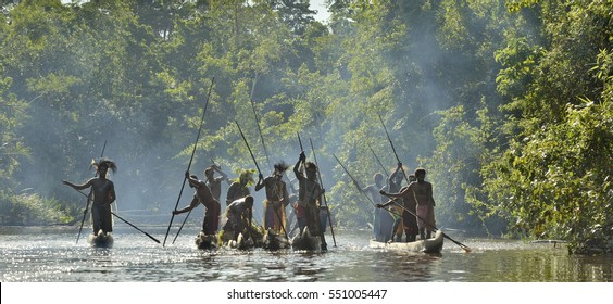 INDONESIA, IRIAN JAYA, ASMAT PROVINCE, JOW VILLAGE - MAY 23: Silhouettes of asmat warriors on the boats. Canoe war ceremony. Headhunters with spear-oar in war paint. New Guinea, Indonesia.May 23, 2016