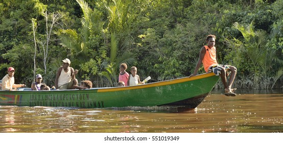 INDONESIA, IRIAN JAYA, ASMAT PROVINCE, JOW VILLAGE - MAY 16:  Local men float in the wood canoe with engine on the river in wild river of deep jungle New Guinea Island, Indonesia. May 16, 2016