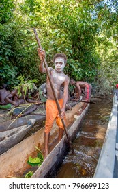 INDONESIA, IRIAN JAYA, ASMAT PROVINCE, JOW VILLAGE - JUNE 13: Young teenage boy from Asmat tribe with oar on the canoe. Papuan Tribe Asmat Territory. New Guinea Island, Indonesia. June 13, 2016