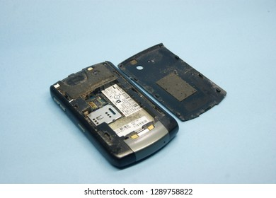 Indonesia January 2019 - Used and Broken Blackberry Curve 8310 Titanium Grey back view with out battery, dirty dusty ugly isolated on blue background