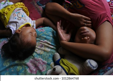 Indonesia -January 22, 2018: Unidentified beggar sleeping on the outskirts of the capital's road with his son on January 22, 2018, Jakarta, Indonesia