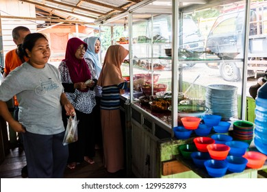 Indonesia - January 27, 2018: A consumer is taking food at a traditional self service street warung in Indonesia or warteg