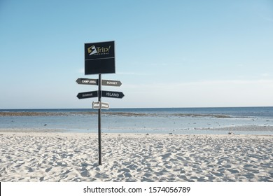 Indonesia, June/19/2019: Travel destination board, direction wooden signboard or signpost at the white sand beach with a clear blue sky background
