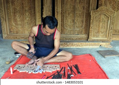 Indonesia man wood carver carving sculptures in Mas, Bali Indonesia.