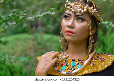 INDONESIA, PONTIANAK - March 27, 2020: Photographer / Model Photography - A very beautiful princess with a glamorous and unique gold dress and crown with colorful stones on her dress. Jungle photo