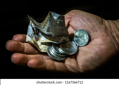 Indonesia rupiah small bill and coins in the hand of an asian person isolated. Concept of begging for leaving, poor person.