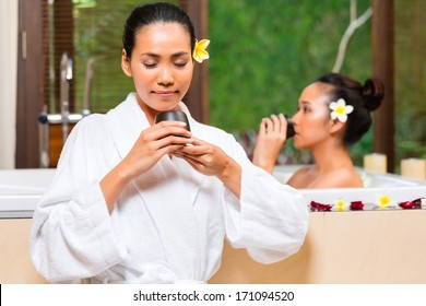 Indonesian Asian women in wellness beauty day spa having aroma therapy bath and drinking herbal tea for detox