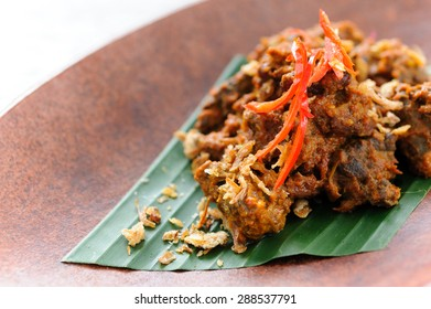 Indonesian beef rendang garnished with fried shallots and red chillies.