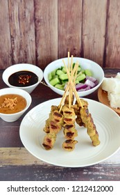 Indonesian chicken satay or Sate Ayam  with lontong. Served with sweet soy sauce, peanut sauce and pickles cucumber and onion