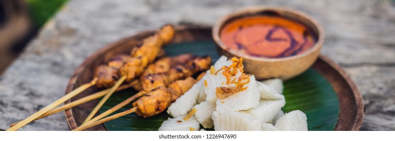 Indonesian chicken satay or Sate Ayam served with lontong, soy sauce and peanut sauce lifestyle food BANNER, LONG FORMAT
