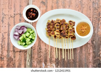 Indonesian chicken skewer or Sate Ayam  with pickles cucumber and onion. Served with sweet soy sauce and peanut sauce