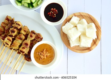 Indonesian chicken skewer or Sate Ayam served with lontong, cucumber, onion, soy sauce and peanut sauce