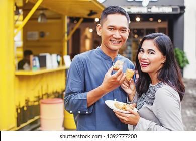 "Indonesian couple eating traditional street food ""jajan"""