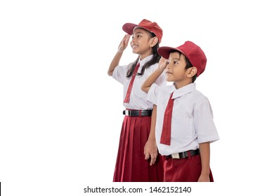 indonesian elementary student wearing uniform giving salute while indonesia flag being raised