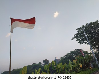 Indonesian flag fluttering in the wind with background - sky, green tree