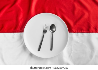 Indonesian Flag with round white plate knife and fork.