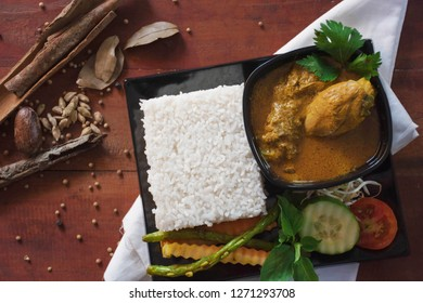 indonesian food ayam kari or chicken curry, is a food made from chicken soaked with herb and spices sauce, presenting with rise, bean sprouts, tomato, cucumber, carot and long beans as vegetable
