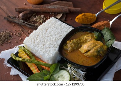 indonesian food ayam kari is chicken curry, is a food made from chicken soaked with herb and spices sauce, presenting with rise, bean sprouts, tomato, cucumber, carot and long beans as vegetable