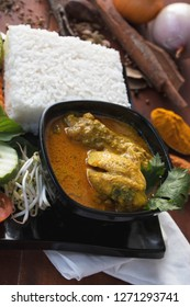 indonesian food ayam kari, side view of a chicken curry, is a food made from chicken soaked with herb and spices sauce, presenting with rise, bean sprouts, tomato, cucumber, carot and long beans