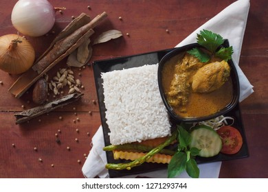 indonesian food ayam kari, top view of a chicken curry, is a food made from chicken soaked with herb and spices sauce, presenting with rise, bean sprouts, tomato, cucumber, carot and long beans