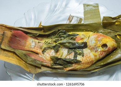 Indonesian food: pepes ikan nila (steamed nile tilapia with spices). Spices are smeared on tilapia's body, wrapped with banana leave, and then steamed. On top of a glass plate and white tablecloth.