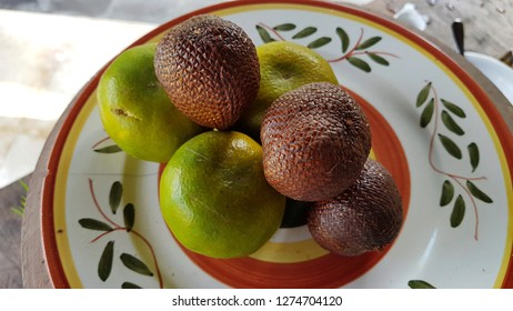 Indonesian fruit, Orange, and Salak. The fruit on the plate. Fruit in shade.