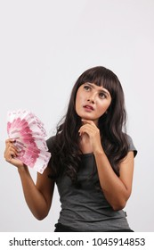 indonesian girl holding money rupiah thinking for shopping online market. indonesian women leaning on a white wall. Casual insonesian woman thinking looking up in grey shirt.