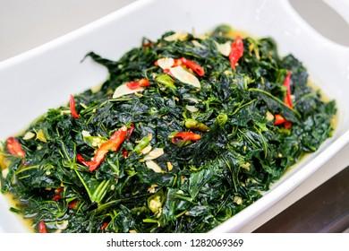 Indonesian home made veggie tumis daun singkong or stir fry cassava leaves