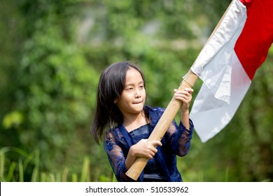 Indonesian Juvenile Swings Her Red-White Flag