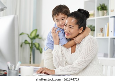 Indonesian little boy hugging his mom, who is computing in home office