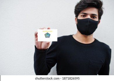 Indonesian man wear all black with face mask hold North Sulawesi flag in hand isolated on white background. Provinces of Indonesia coronavirus concept.