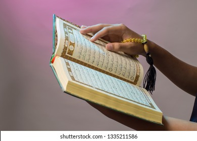 Indonesian muslim. The open Qur'an is held by the hand holding the prayer beads (tasbih). The Qur'an is the holy book of Islam.
