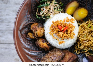 Indonesian nasi campur with fried chicken, noodles, eggs, tempeh and vegetables.