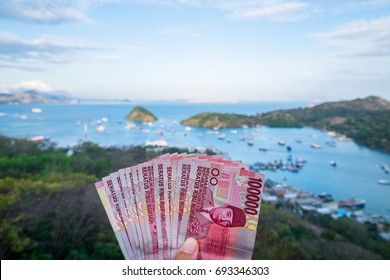 Indonesian rupiah money in hand with beach background in Labuan Bajo, Flores Island, Indonesia