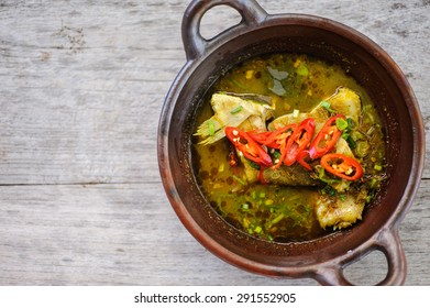 Indonesian style fish curry garnished with red chillies.
