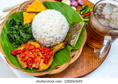 Indonesian traditional food ayam Geprek or fried chicken served with nasi, es teh manis, tahu, lalapan daun singkong, sambel terasi on banana leaves