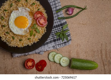 indonesian traditional food, egg fried rice with vegetable cuts, tomatoes, cucumber, chili, and empty space