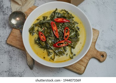 Indonesian traditional food 'Gulai Daun Singkong' or made from Tapioca or cassava leaves cooked with coconut milk, selective focus