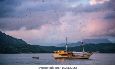 Indonesian traditional ship in the ocean at sunset twilight.  Ocean and mountains Landscape. Komodo Island. Moluccas, Indonesian Maluku, Spice Islands, Indonesia