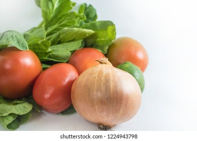 Indonesian typical vegetables and food ingredients: bok choy, tomatoes, key lime, onion; on a white background
